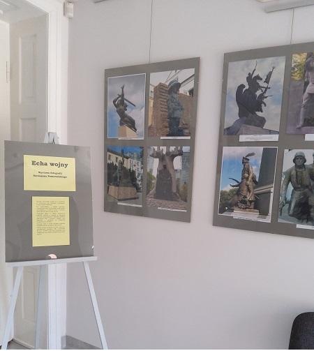 """Zdjęcie przedstawia sztalugę z planszą tytułową wystawy """"Echa wojny"""""""